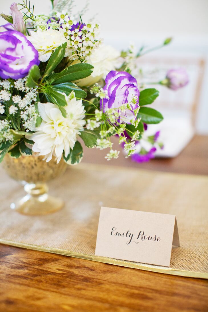 Table centerpieces included purple anemones, white roses, white dahlias, purple mini callalilies, and berries held in gold bowls. Hand-calligraphed place cards noted each guest's seat.