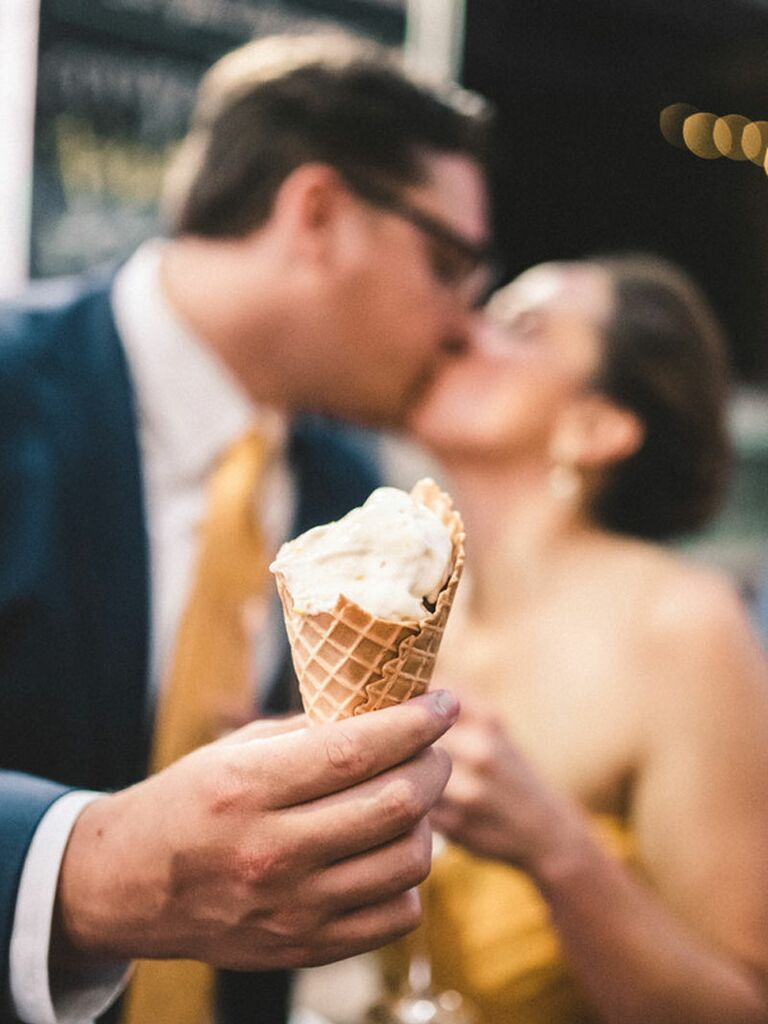 Bride and groom eating ice cream during summer wedding reception