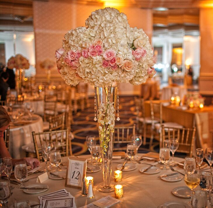The couple chose tall centerpieces of floating white cymbidium orchids, white hydrangeas and pink garden rose accents for their reception.