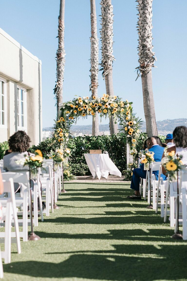 Oceanfront wedding ceremony with sunflower altar arch