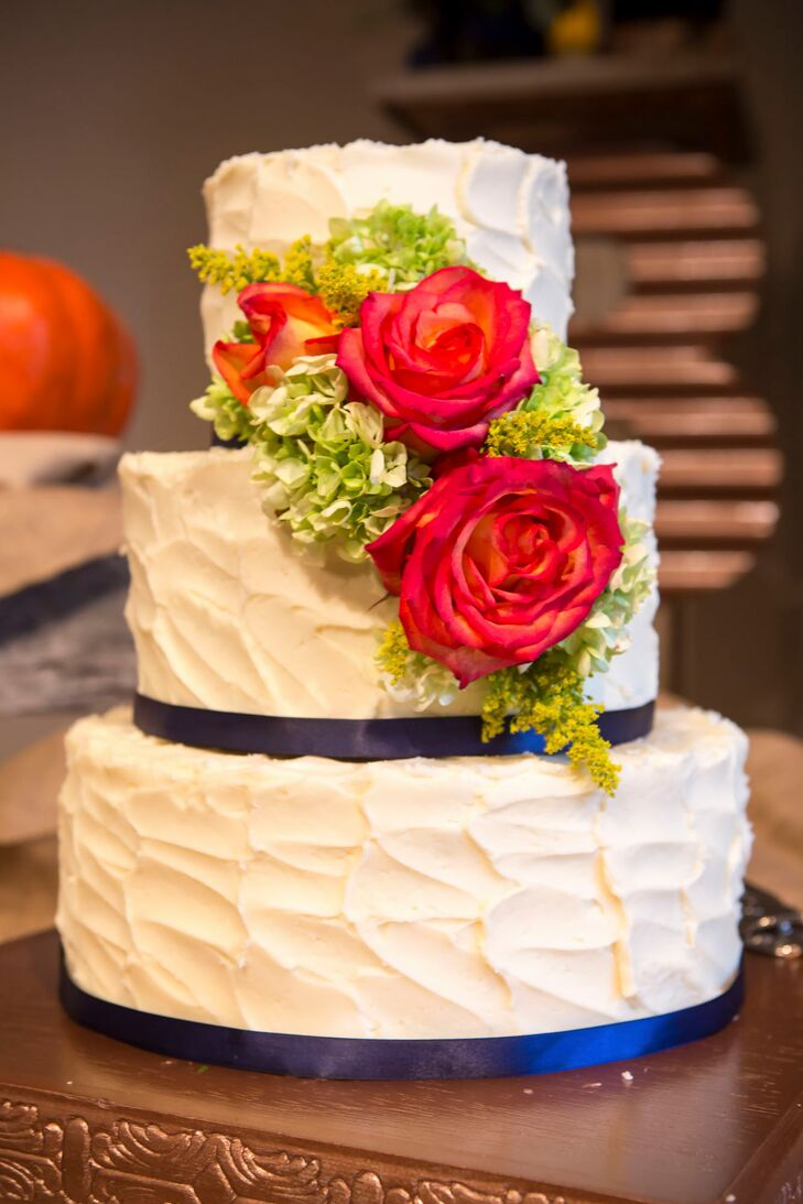 Cakes By Iris baked a three-tier buttercream cake that grabbed onto the theme with a little color. Navy ribbon wrapped around the ivory confection. Red roses and green hydrangeas also cascaded down the front.