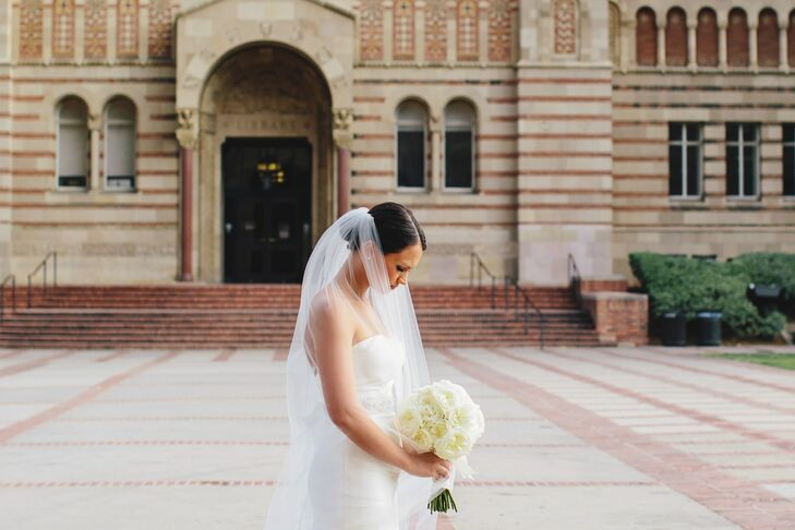 Madeline wore an ivory tulle veil with her updo hairstyle. She held an ivory garden rose bouquet.