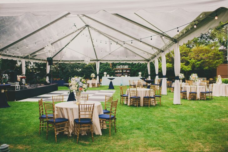 At the reception, each table was covered in navy and ivory linens while mercury-glass candles and dramatic hydrangea centerpieces sat atop. Cafe lights were strung throughout the trees and along the clear-top tent to create a romantic garden atmosphere.