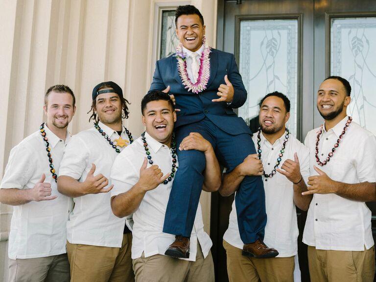 groomsmen in Polynesian clothing holding groom on their shoulders