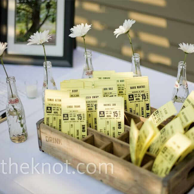 Kelly designed the escort cards to look like old-fashioned movie tickets. She and a bridesmaid printed them at Kinko's and spent an afternoon cutting them down to size. Kelly displayed the cards in an old soda-pop crate she and Jeff found in their Brooklyn neighborhood. Vintage soda bottles surrounded the crate, each with a daisy inside it.
