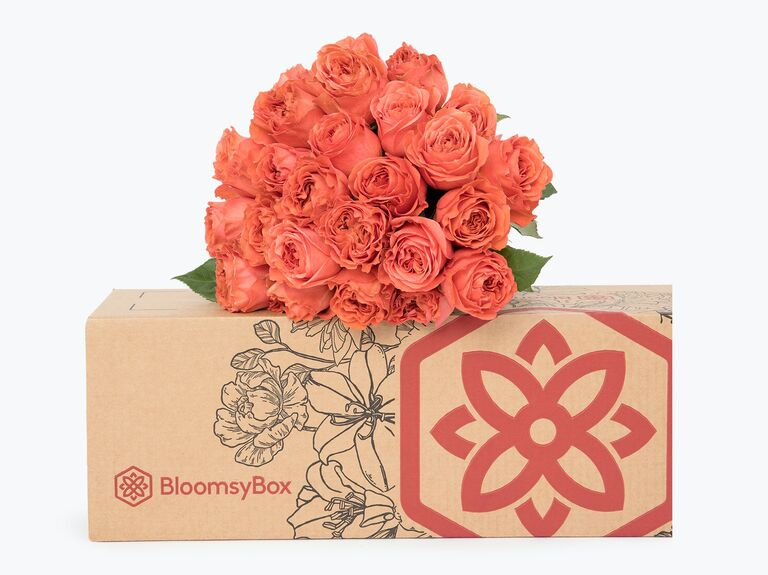 Coral-hued bouquet of roses pictured on top of BloomsyBox delivery box