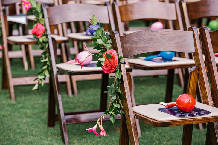 Caroline and Christopher's aisle decor matched the wedding arch and added extra color to the natural setting of St. Augstine Green in Rosemary Beach, Florida. Mini-arrangements of greenery, fuchsia garden roses and pink tuber roses accented every row of wooden folding chairs.
