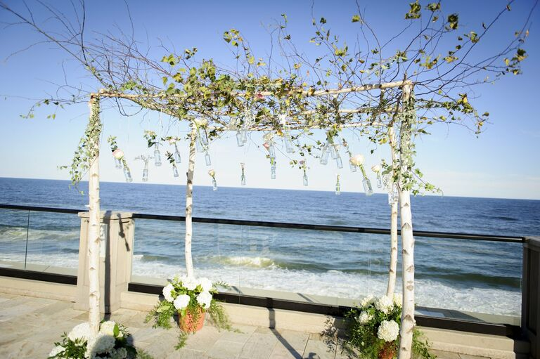 Chuppah with small glass bottles and single blooms