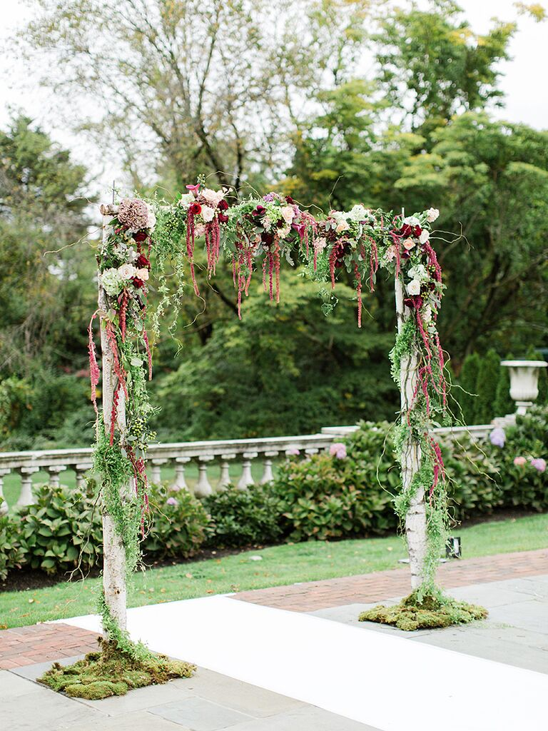 A rustic moss draped birchwood arch wrapped in vines for an outdoor wedding