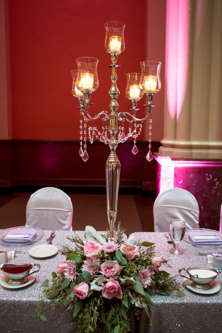 Tall glass candelabras stood in the center of each table with lit candles in each holder. At the base of each vessel, cascading roses fell over the side of the table.