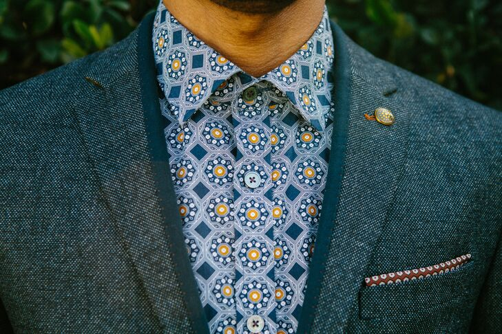Jerrold wore a blue and burnt orange patterned shirt with his gray suit, all designed and purchased from  Ted Baker.