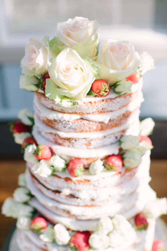 "The couple's cake was a naked strawberry cake topped with white roses. ""I'm not a fan of a lot of icing, so this was the perfect choice for me,"" Megan says."
