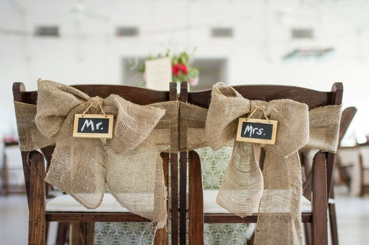 Burlap sashes were tied in bows at the back of the bride and groom's chairs during the reception and accented with hand-written Mr. and Mrs. chalkboards.