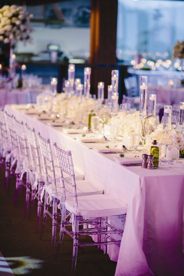 Contemporary clear reception chairs lined each table.