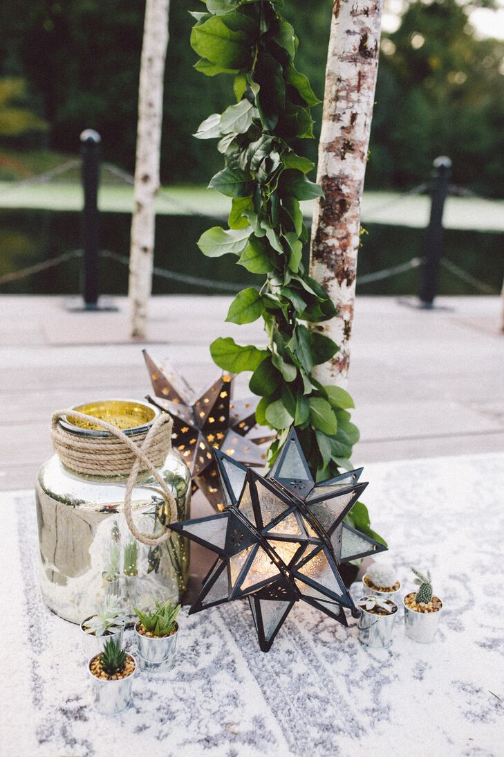 Cacti, Mexican star lanterns and mercury glass vases rested at the base of the birch wedding arch, which stood atop a rug and was wrapped in a live salal garland.