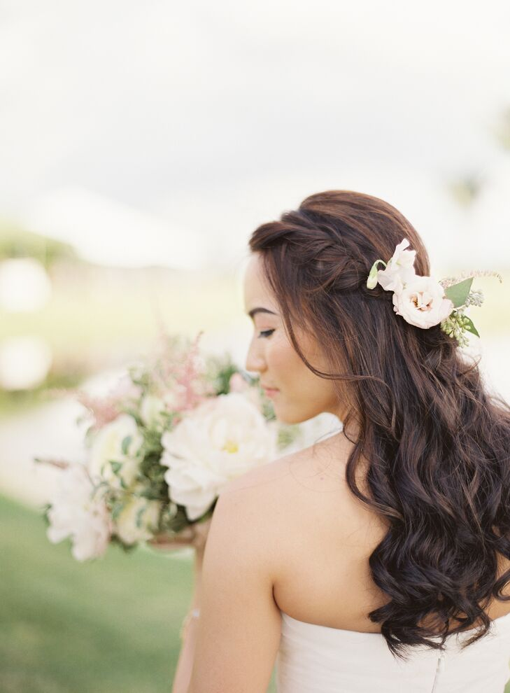 """As she usually does not wear makeup, Joyce opted for a natural look, She wore her hair down and in a curls with a simple braid. """"During the ceremony, we incorporated a few flowers hugging the braid as well,"""" says Joyce."""