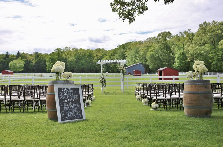 """With the help of Laura and Gary's florist, Broad Brook Gardens, low arrangements of white hydrangeas in clear-glass cylinder vases lined the ceremony aisle and topped two rustic wooden barrel accents. """"I wanted a shabby chic/romantic theme, but I also wanted to tie in the farm. So, there were some rustic touches,"""" Laura says."""