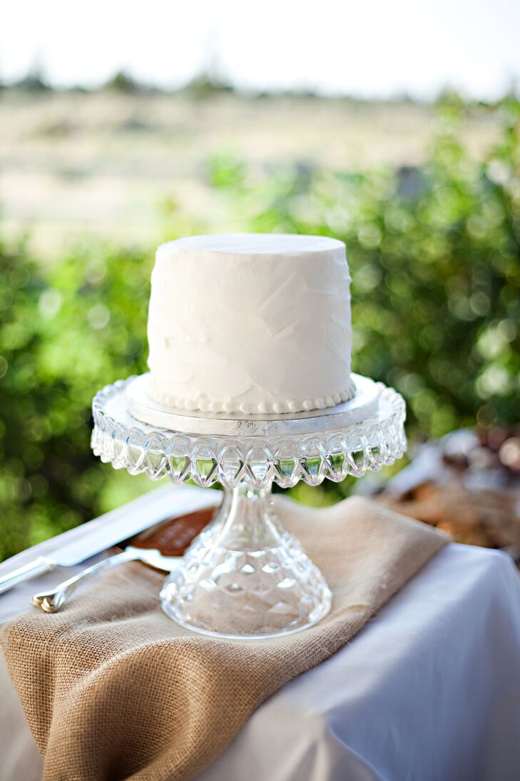 Sara and Kris used their small white cake for cutting, beaded with icing at the bottom of the dessert. The simple yet sweet cake sat on top of a glass stand, with a piece of burlap underneath.