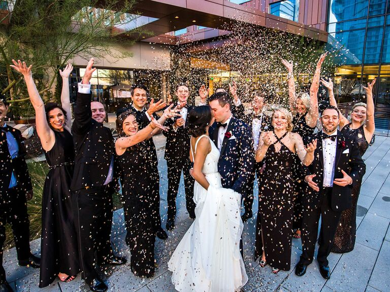 Bride and groom kissing under confetti toss thrown by wedding party