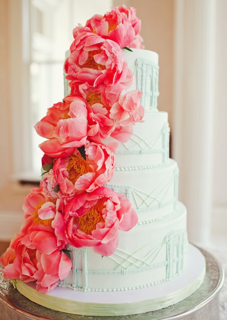 Classic white wedding cake with bright pink peonies