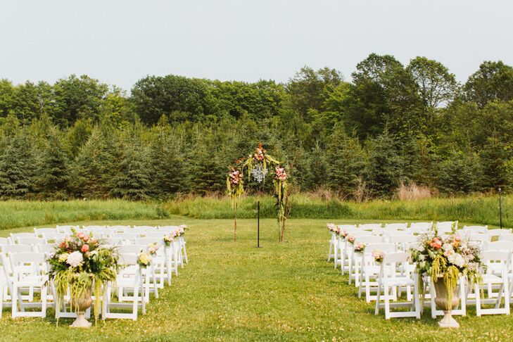 Katherine and Kevin took full advantage of the Woodwalk Gallery's beautiful grounds and the beautiful weather by hosting their ceremony outdoors. The couple gathered their closest family members and friends in the lush field behind the barn, where they profited from views of lush forest, wild-flower-flecked fields and the calm waters of the nearby lake.