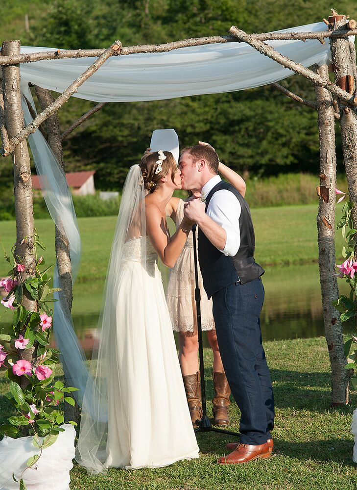 Mary and Sam shared their first kiss as husband and wife under a rustic wooden arch made out of tree branches and decorated with white drapery and pink flowers.