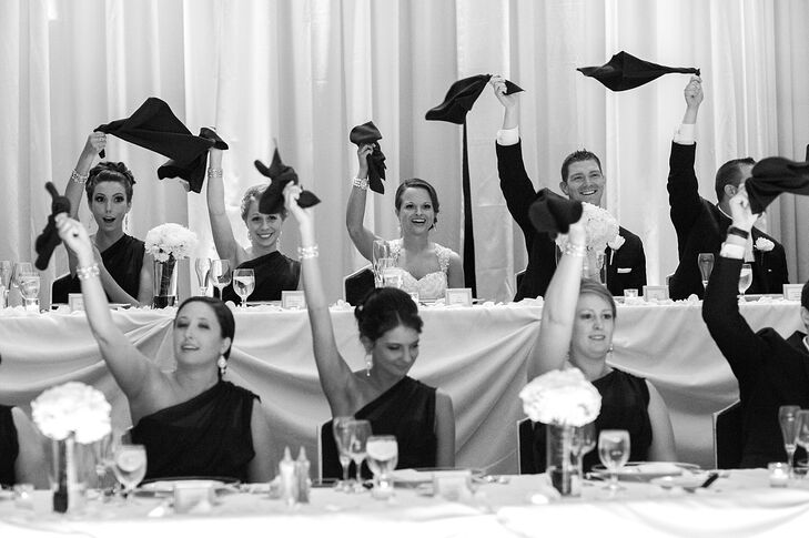 Dresses in black off-the-shoulder dresses, Kristen's bridesmaids playfully waved black napkins around to signify the start of a speech during the couple's reception.