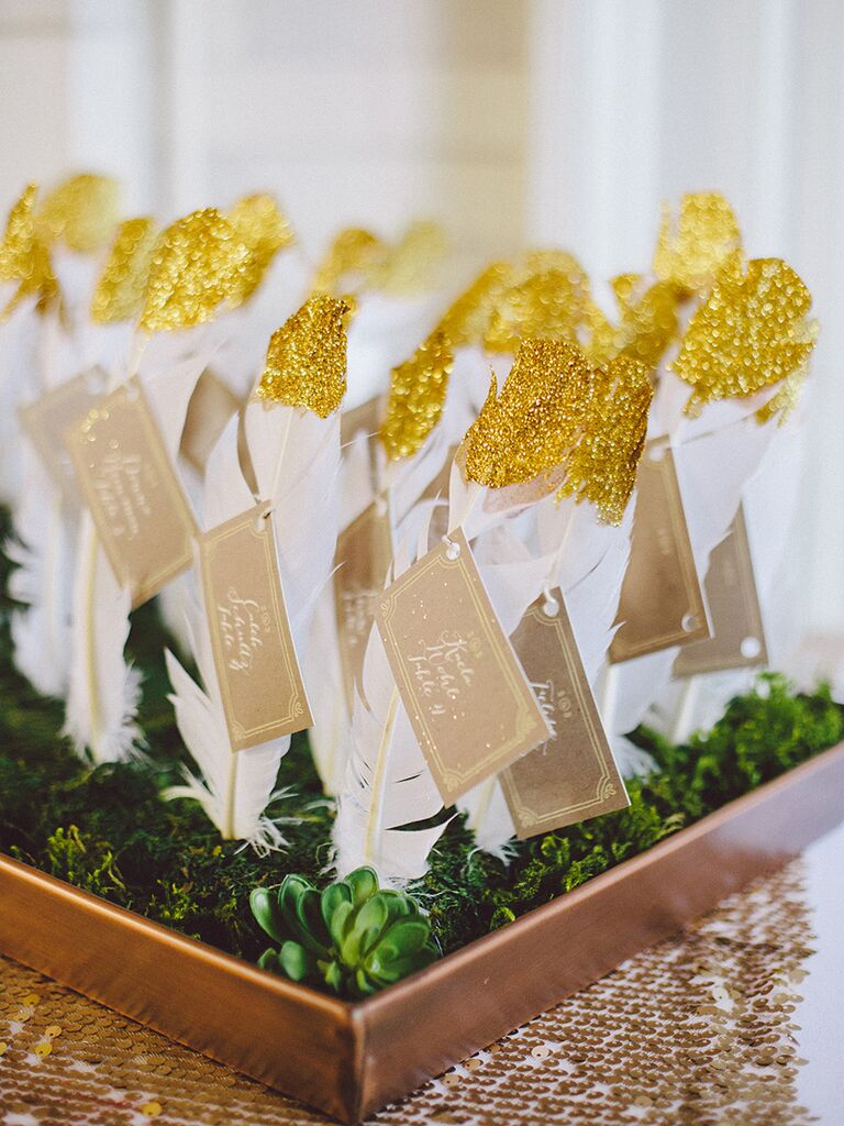 DIY wedding reception escort cards with gold painted feathers