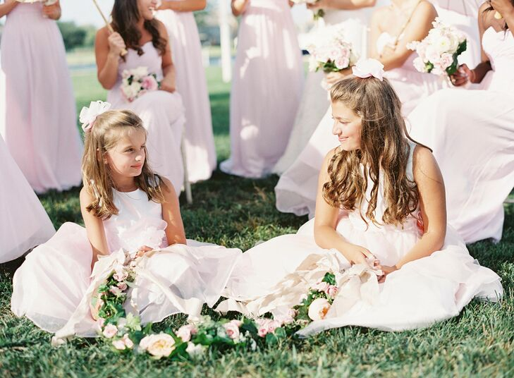 Flower girls wore white and pink organza dresses that were embellished with a flower at the waist. As they walked down the aisle, they carried a garland of fresh flowers rather than throw petals.