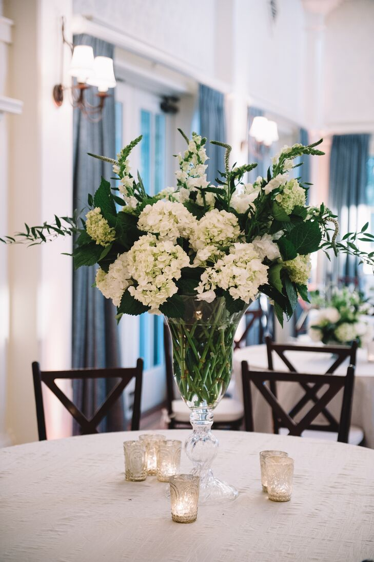 Florist Sue Burden crafted the simple greenery-rich centerpieces, which perfectly fit the white and green palette at The Inn at Pinebluff in Bluffton, South Carolina.