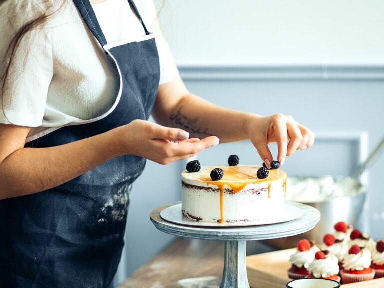 cake baker in blue apron decorating cake