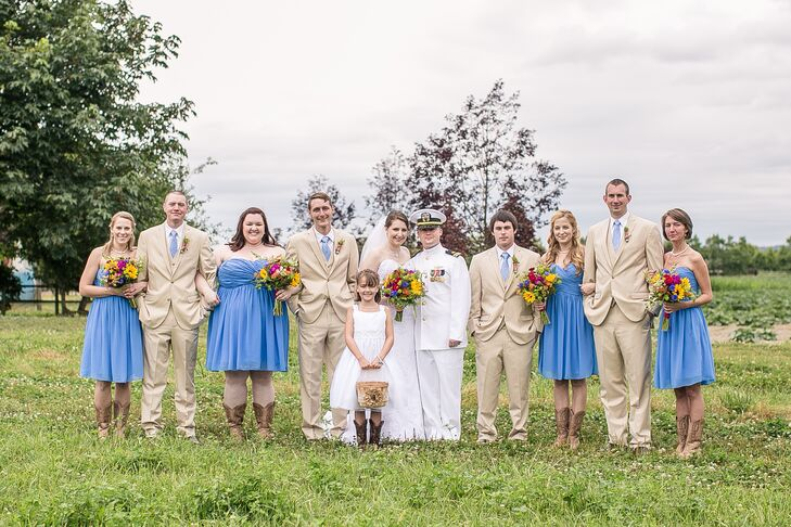 Justine and Josh stood with their wedding party outside at the venue. Bridesmaids wore cornflower-blue, strapless dresses with cowboy boots, while groomsmen sported tan suits with blue ties to match the bridesmaids.