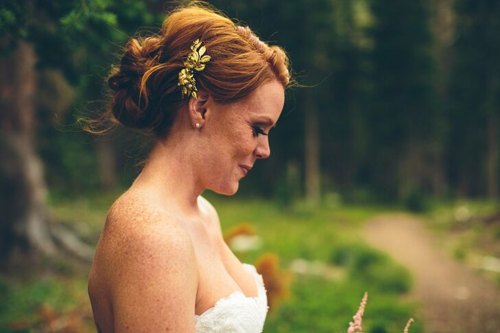 Faith's hair was pinned back with a golden, floral hair pin and configured in a low updo.