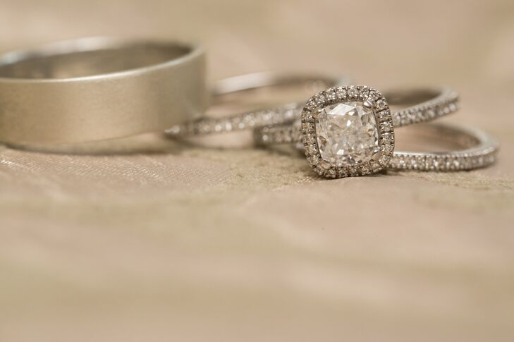 Angela and Michael had gone together once or twice to look at rings and find a style she'd like. She loved the Halo setting so Michael decided to go with a cushion cut in a halo setting in white gold. Their wedding rings were silver and Angela's was diamond to match her engagement ring.