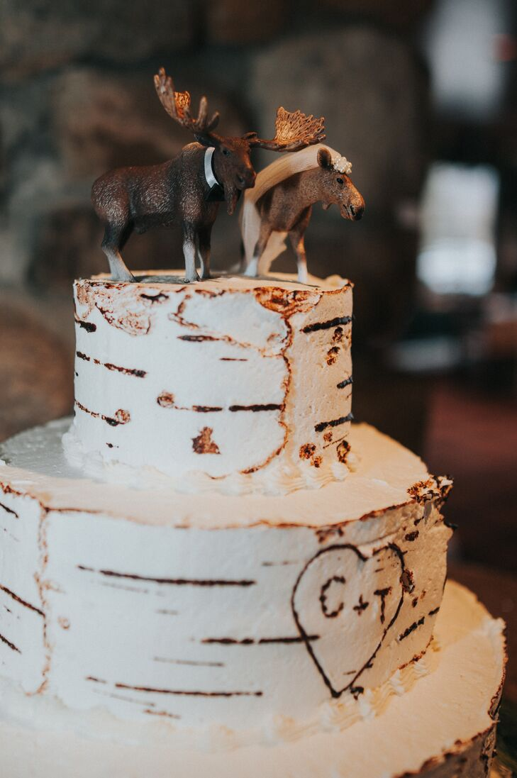 """We did a three-tier cake with two maple layers in another callout to the wedding's Adirondack style,"" Cait says. ""The cake was frosted in vanilla buttercream that was styled to look like birch tree bark and had our initials (C+T) carved into it. A bride and groom moose topped the cake as another homage to the wedding's location and our love of moose!"""