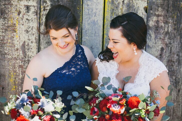 The bridesmaid's deep blue one-shoulder dress offset the red and white floral arrangements.