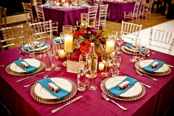 The reception tables had small centerpieces of mixed pink and purple flowers with pink linens. Instead of table numbers, the couple chose names of cocktail drinks and listed the ingredients underneath. Glass chargers and teal napkins finished off the look.