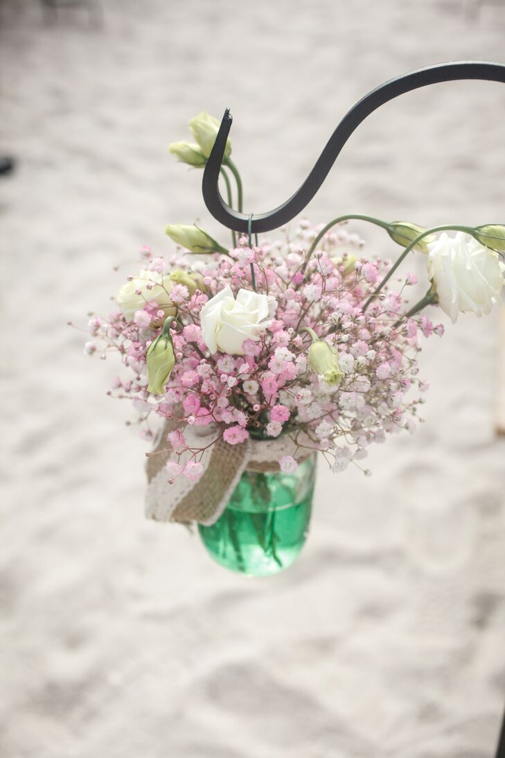 Chelsea and Steve lined their ceremony aisle with mason jars filled with green  water, pink baby's breath and white roses.