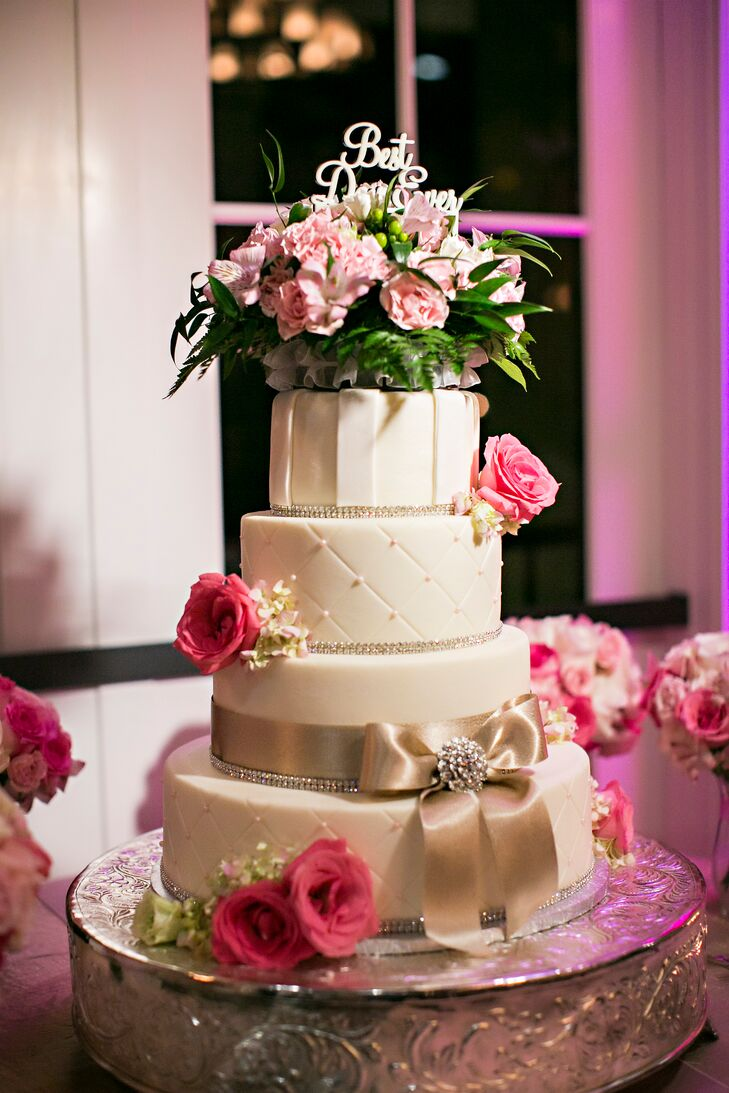 Kelley and Kegan accented their pink and white floral-covered wedding with a matching wedding cake from Metro Custom Cakes. Each round ivory tier was met with either a quilted design, a champagne bow or stripes for a fun touch as pink roses and tea roses were used as accents.