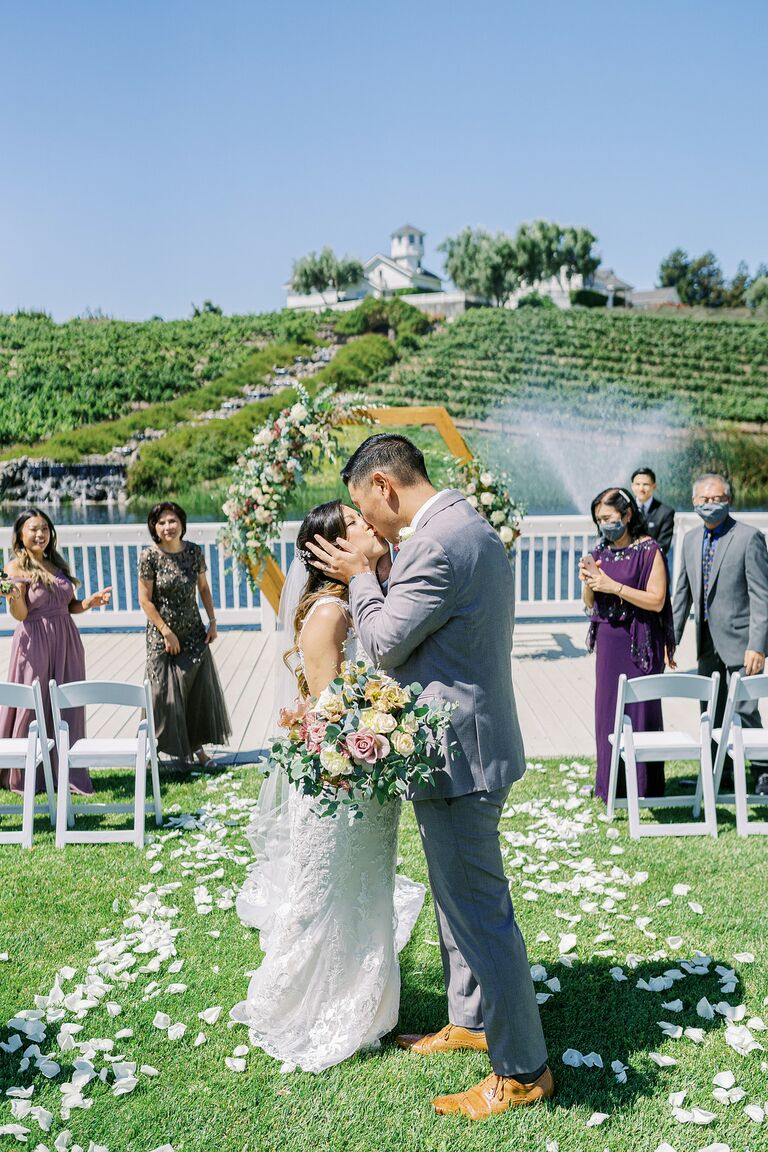 Couple shares kiss during wedding ceremony recessional