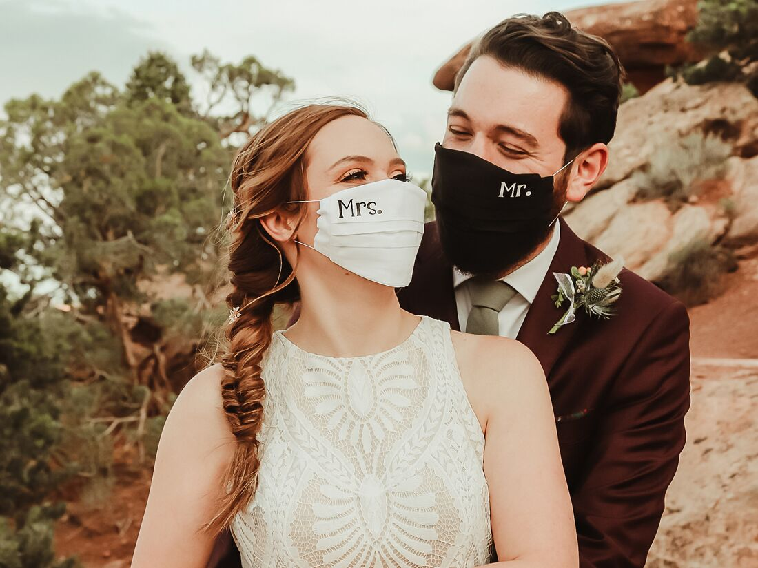 Bride and groom wearing Mrs. and Mr. wedding masks