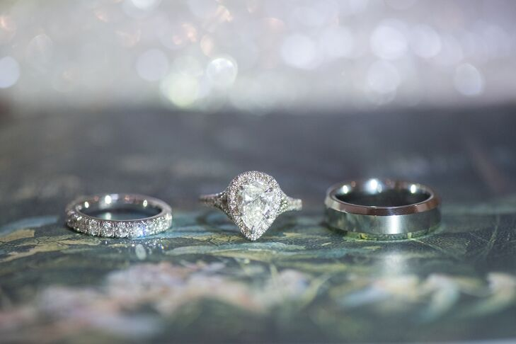 Erin's engagement ring features a center pear-cut diamond from her grandmother. Chris worked with jeweler Norman Landsberg to place it in a unique setting. For wedding bands, Chris wanted a simple design, while Erin opted for a half-eternity band to complement the engagement ring.