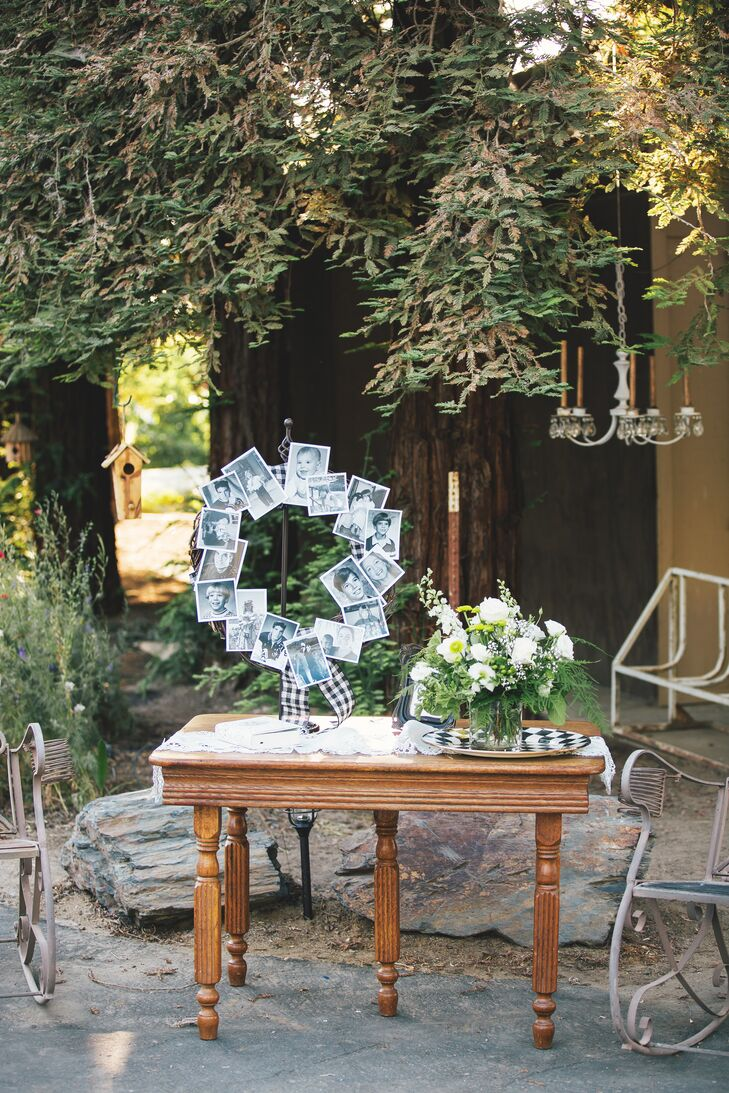 At the reception, a photo collage was displayed in the shape of a wreath, displaying old family photos. On the same table, there was a lush ivory and green flower arrangement.