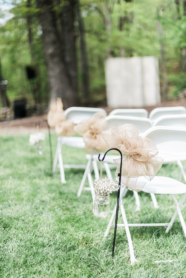Jordan and Austin introduced the wedding's country theme right from the get-go, incorporating rustic elements into the ceremony's design. Along the aisle leading up to the altar where the couple would exchange vows, they placed black shepherd's hooks, from which they hung fresh bundles of baby's breath arranged in mason jars and big burlap bows.