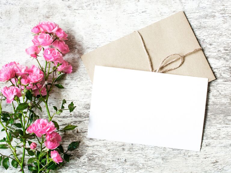 a wedding card filled with wedding wishes of congratulations next to a bouquet of pink flowers