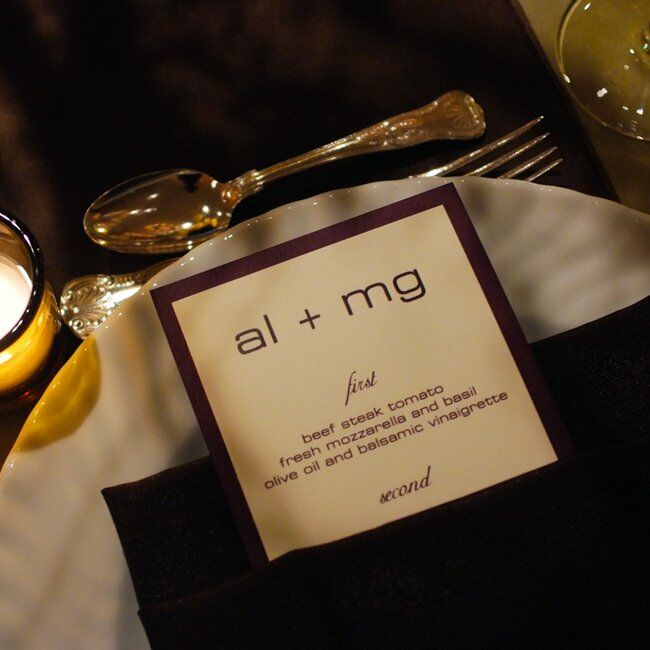 Andrea and Matt's menus, along with many of their other paper items, were created in a deep purple hue and incorporated the couple's logo. Each was tucked inside a deep purple napkin.