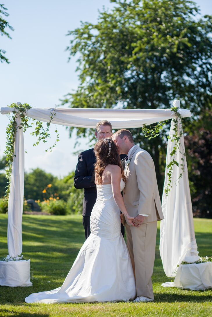 The couple exchanged vows outdoors, in front of an elegant white drape arch.