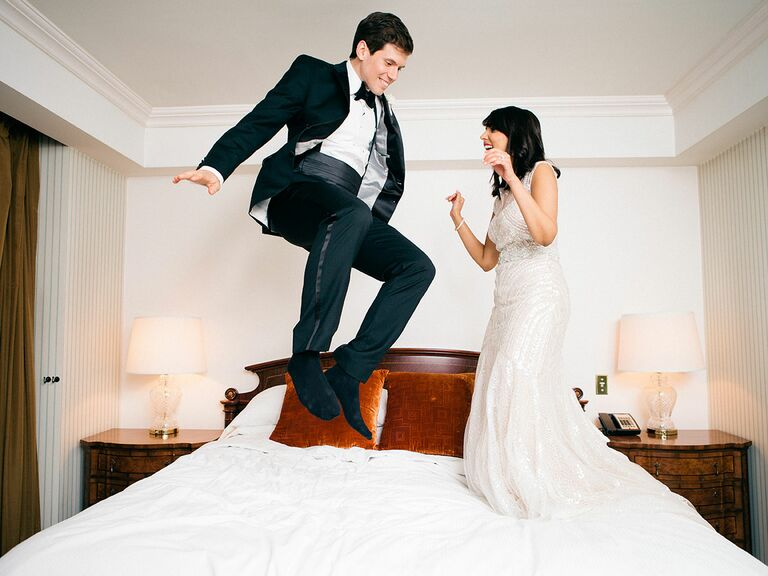 bride and groom jumping on the bed candid wedding photo