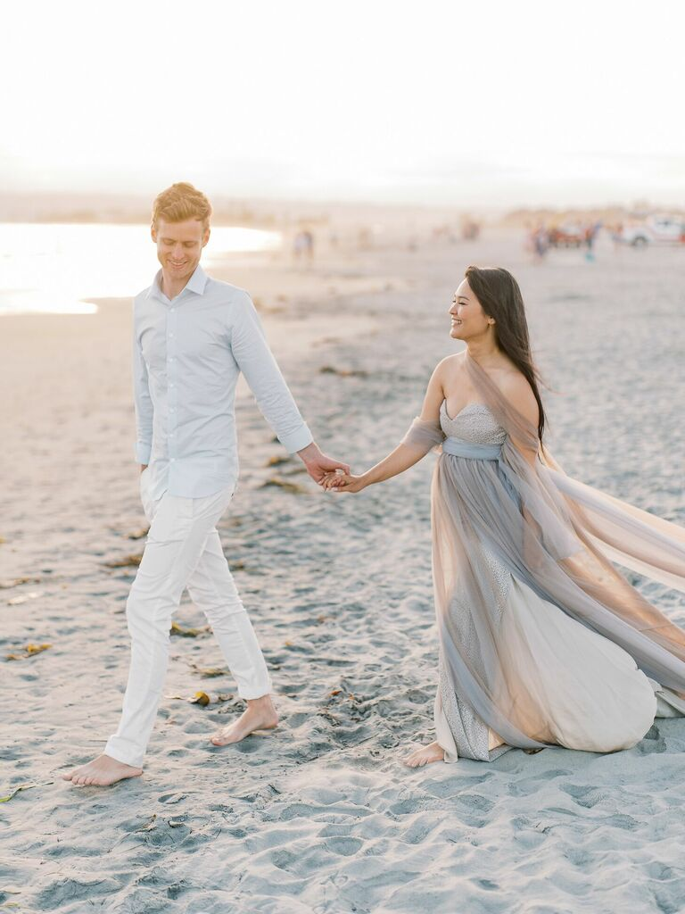 Couple walks hand-in-hand on beach during sunset