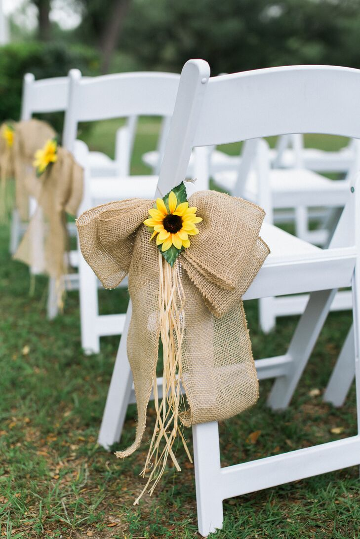 Rustic details were also used during the wedding and first appeared as their aisle decor. Three rows of white folding chairs were paired with large burlap bows and straw that were topped with a single sunflower.